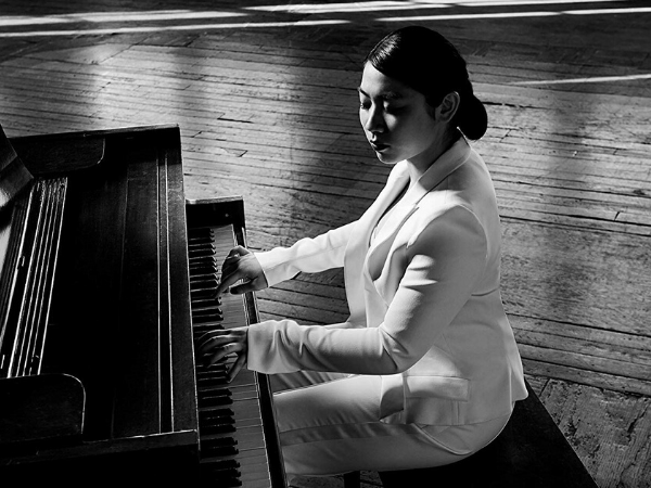 woman playing piano in white suit