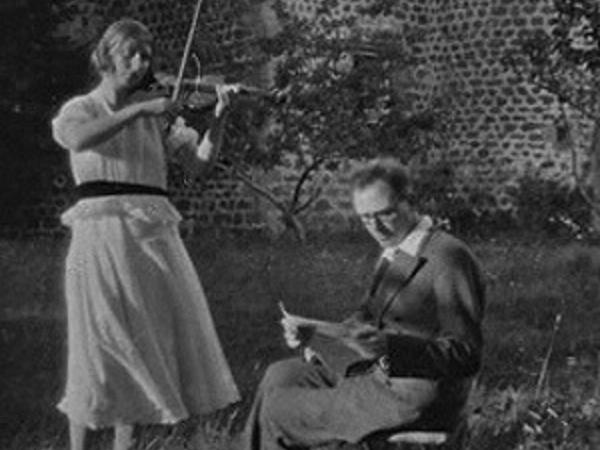 woman playing violin and man writing