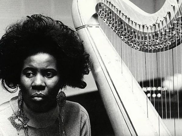 Alice Coltrane sitting next to her harp