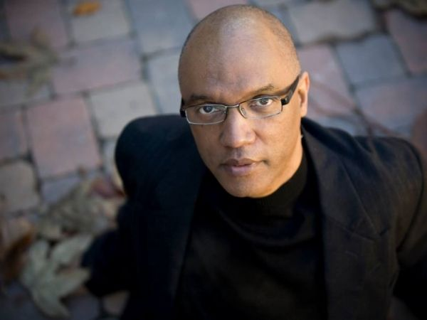 Billy Childs staring up at the camera in a nice suit