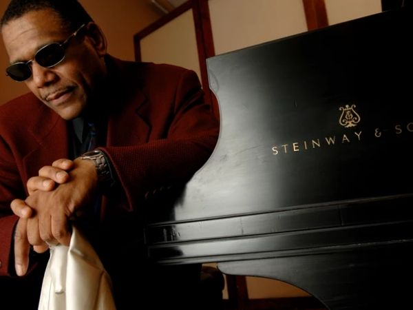 Donal Fox sitting in front of a Steinway piano in a burgundy suit