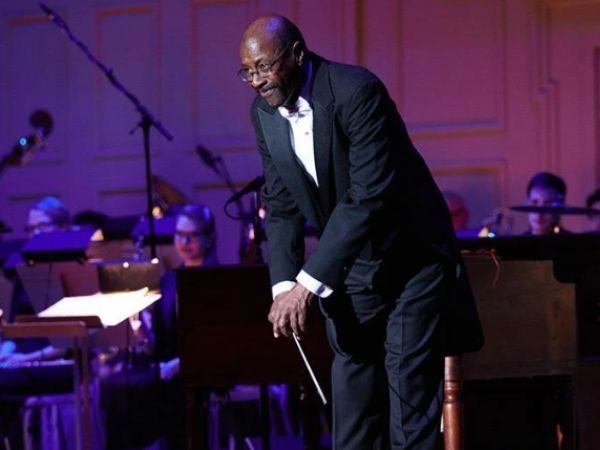Julius P. Williams in a tux and bowing after conducting a performance