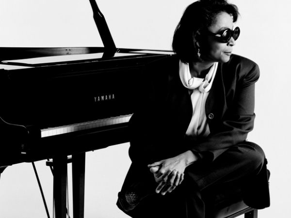 Dr. Valerie Capers sitting in front of a piano in a nice suit