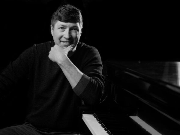 Black and White Photo of Mike Alston sitting at a piano