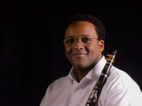Afendi Yusuf holding his clarinet smiling at the camera