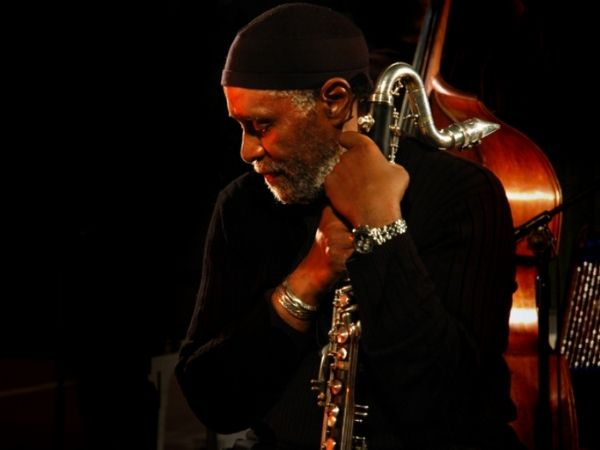 Bennie Maupin wearing all black, holding his bass clarinet on stage pensively