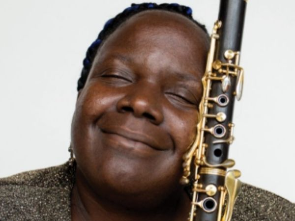 Doreen holding her clarinet that has gold keys and smiling