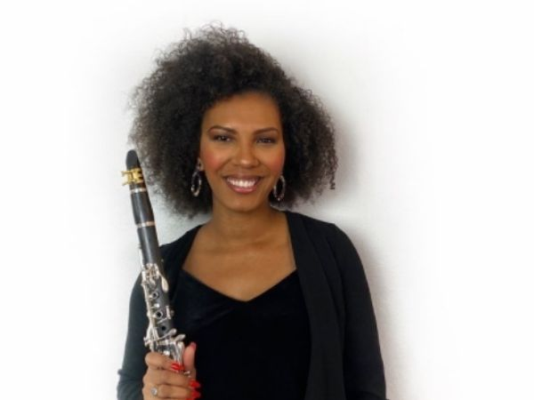 Sahniee Kennedy on a blank background holding her clarinet and smiling