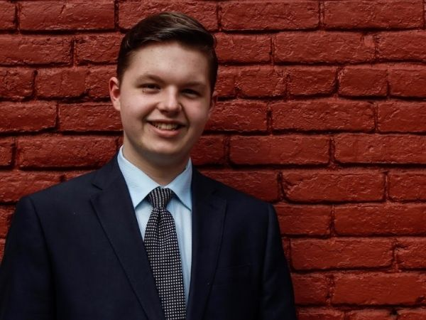Cameron Massey standing against a red brick wall in a suit