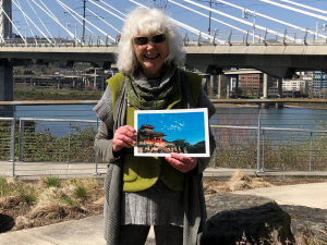 woman with white hair and sunglasses holding a photo of a temple in Japan; behind her is a bridge and a river