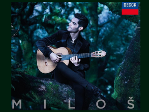 man playing the guitar with a forest in the background